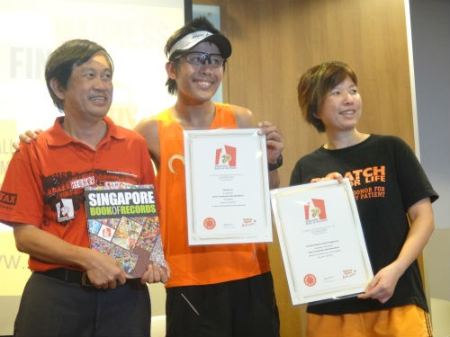 Ah Siao is presented with his certificate from the Singapore Book of Records, for running the most consecutive marathons in Singapore.