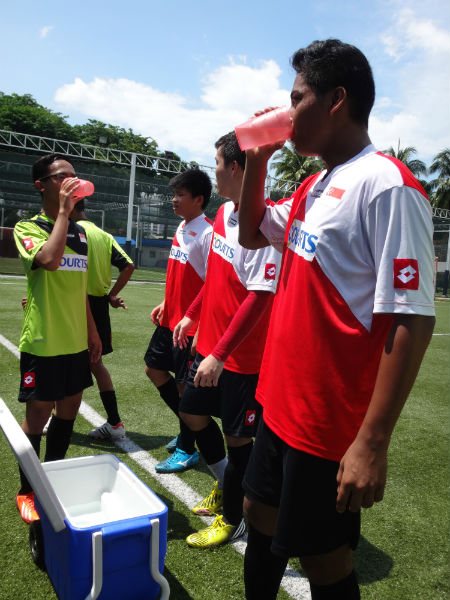 Footballers sipping some water during training.