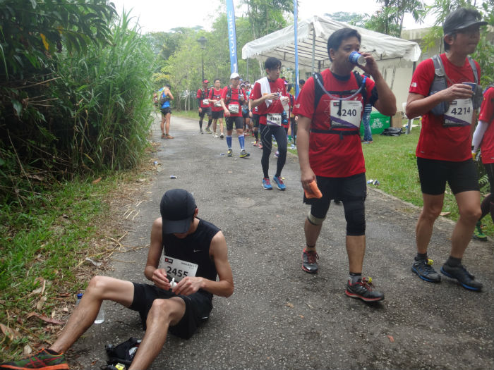 Exhausted runners taking a breather by sitting down or sipping water.