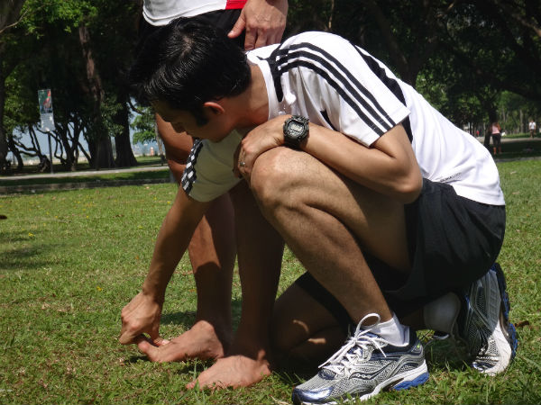 Zaki demonstrates to a runner how to do toe curls.