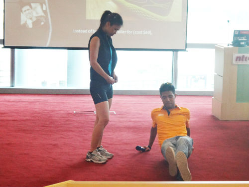 During the workshop, Marcus (in orange) shows a participant one of his stretching exercises.
