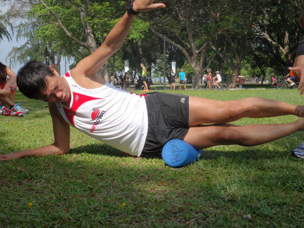 A volunteer is demonstrating how to use the foam roller.